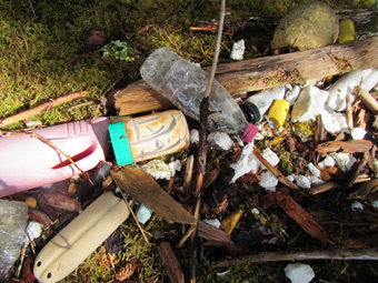 More washed up garbage, including a plastic peanut butter jar.